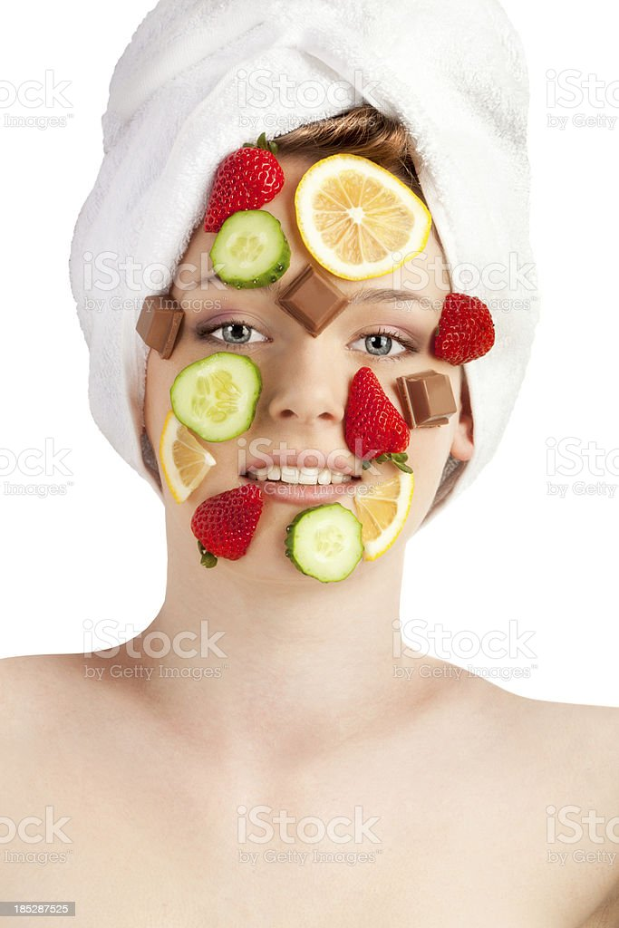 Strawberries, lemons, cucumbers and chocolate on the beautiful face. royalty-free stock photo