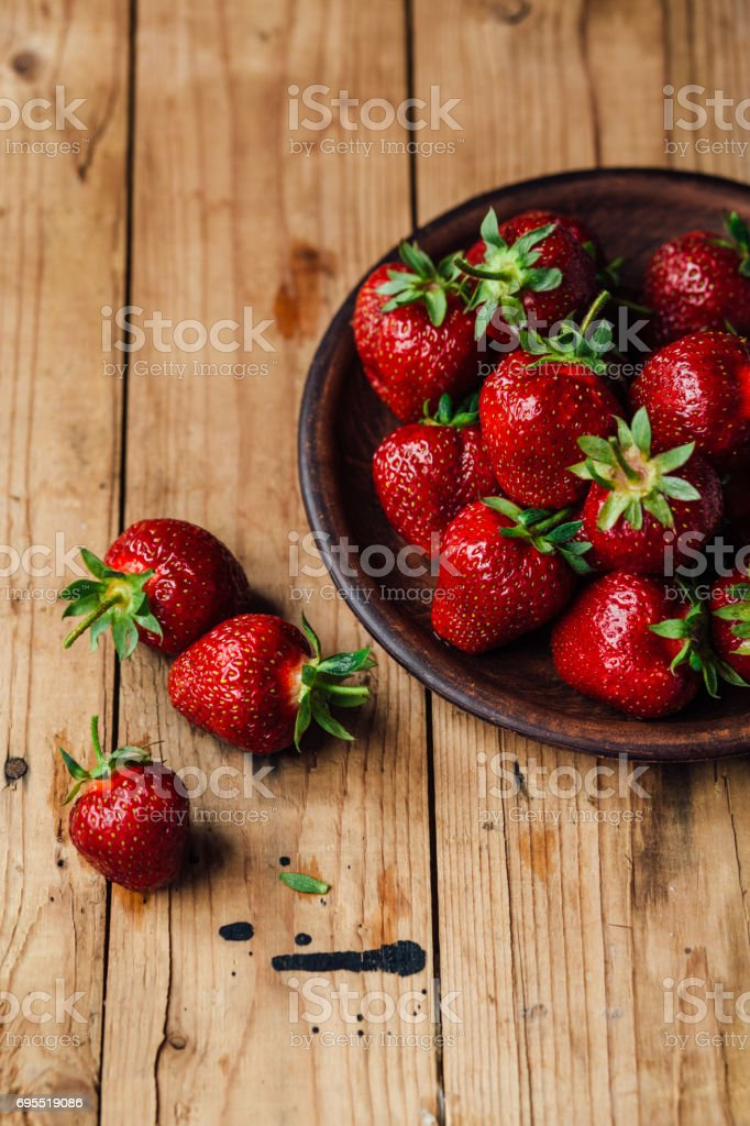 Strawberries on a plate on a wooden table stock photo
