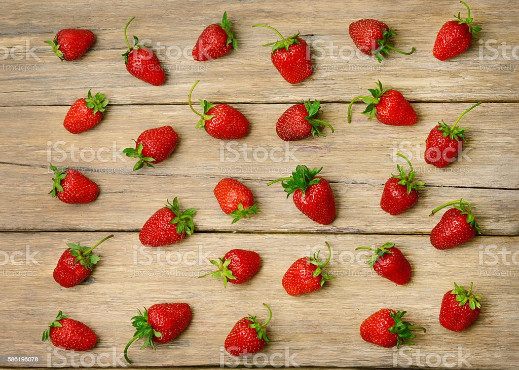 strawberries on a wooden surface background stock photo