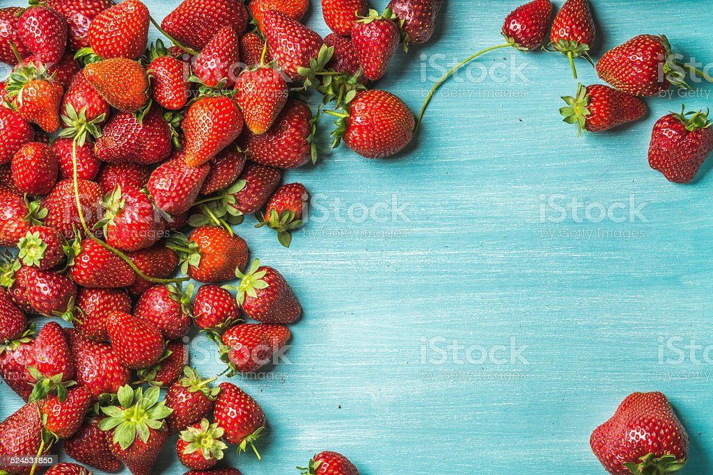 Strawberries over turquoise blue painted wooden background stock photo