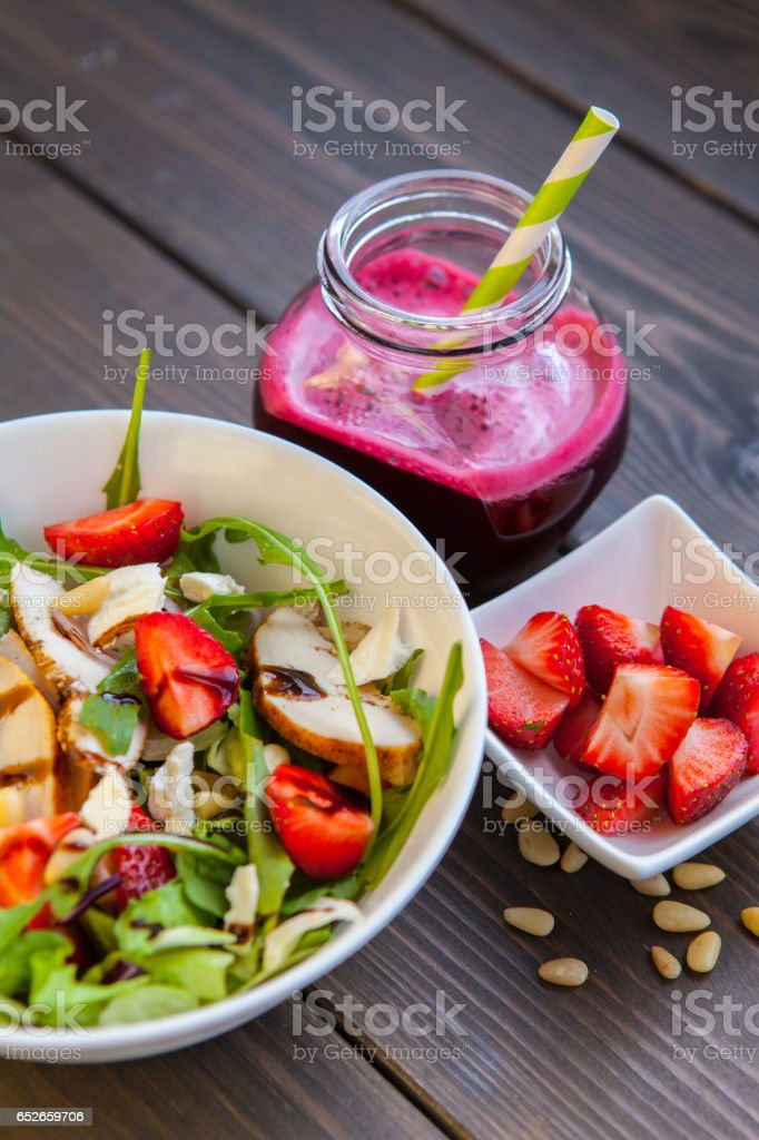 Strawberries salad with pine nuts, arugula and chicken. Beet  fresh juice. Healthy & fitness food. top view stock photo