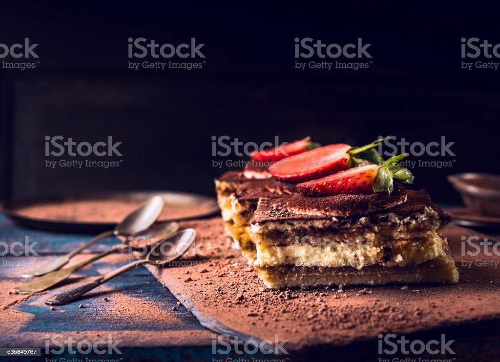 strawberries tiramisu cake with three spoons on dark wooden background stock photo