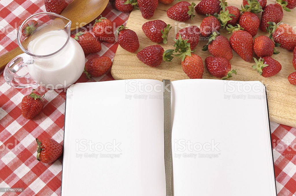 Strawberries with blank recipe book and red check tablecloth stock photo