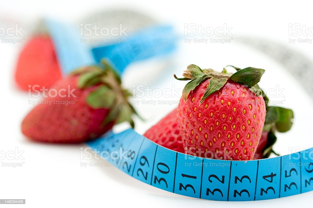 Strawberries wrapped around with a measure tape royalty-free stock photo