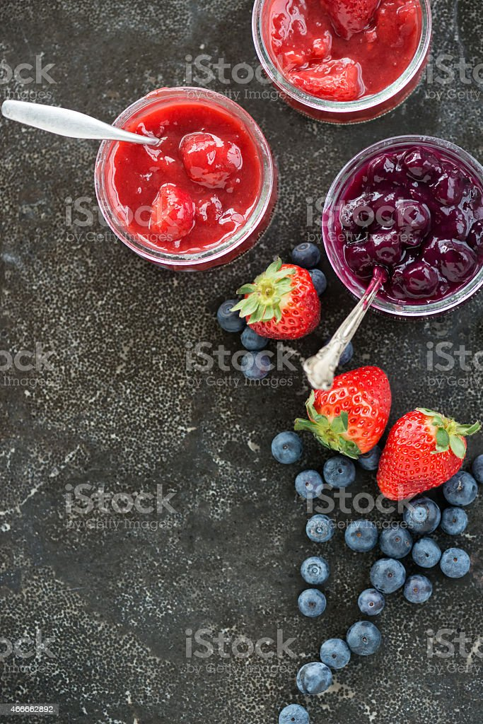 Strawberry and Blueberry Compotes in Glass Containers on Slate Background stock photo