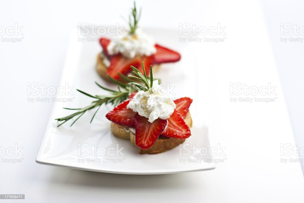strawberry and cream cheese crostini with rosemary stock photo