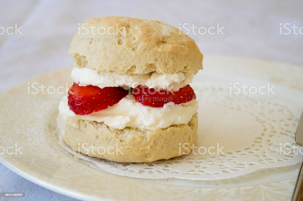 Strawberry and cream scone on a white plate stock photo