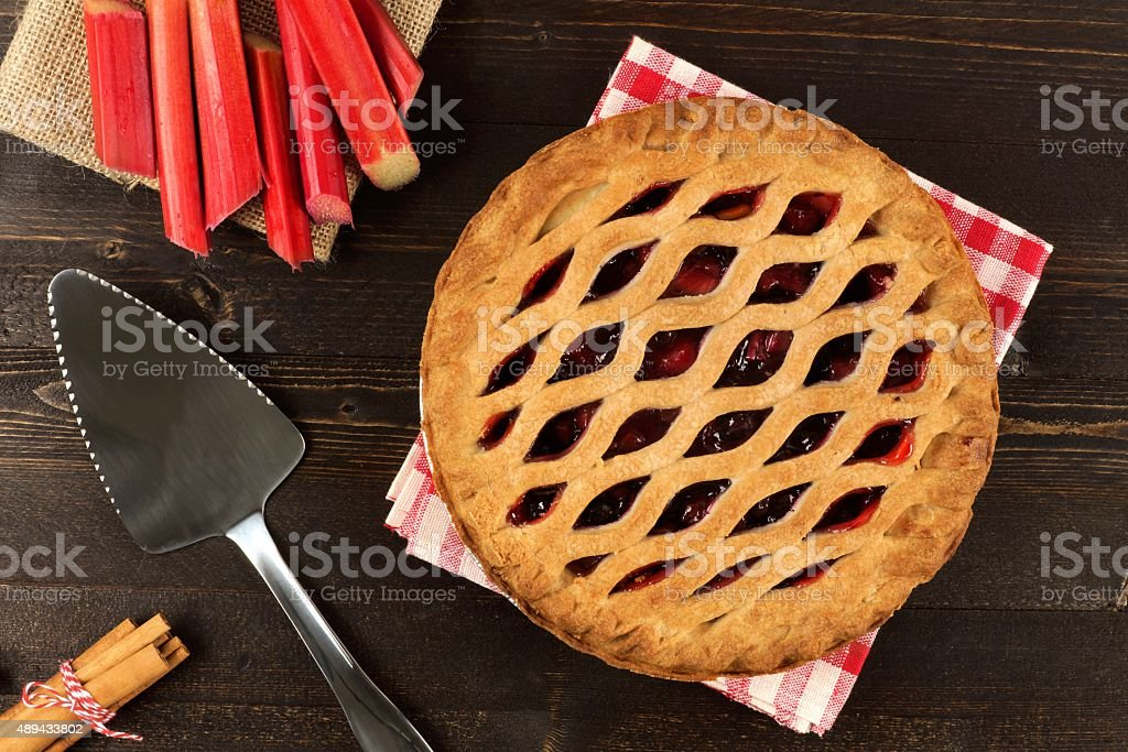 Strawberry and rhubarb pie on dark wood background stock photo