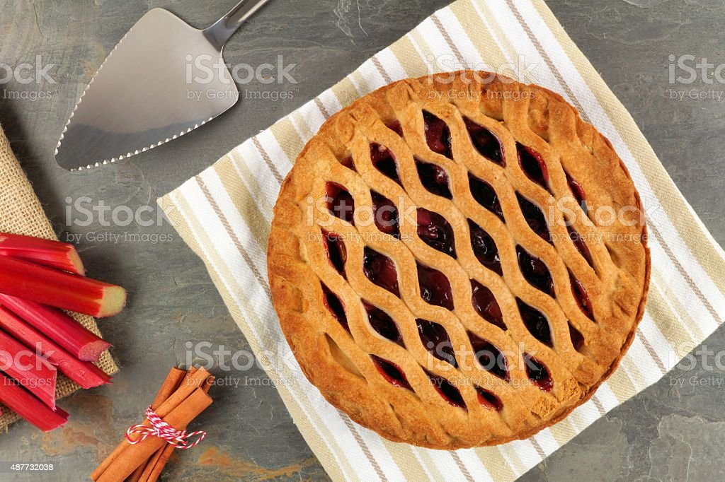 Strawberry and rhubarb pie scene on slate background stock photo