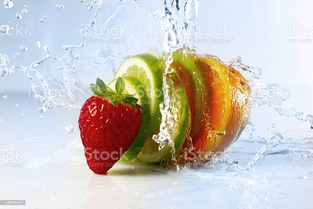Strawberry and sliced citrus splashed with water stock photo