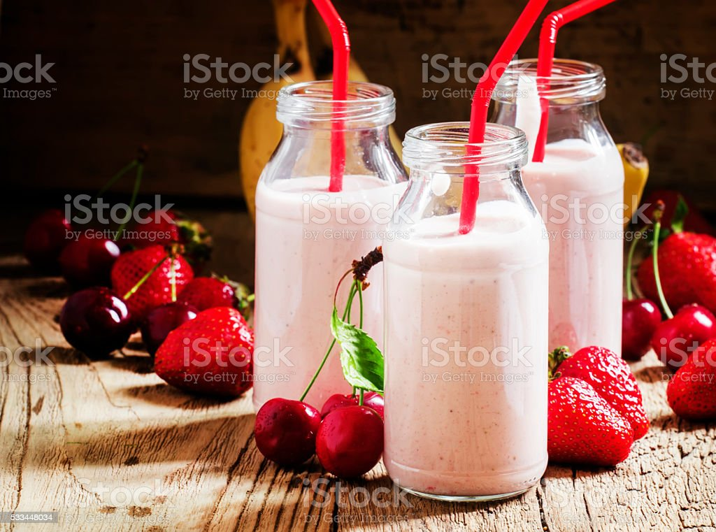 Strawberry Banana smoothie with cherry in glass bottles stock photo