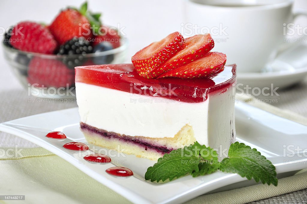 Strawberry cheesecake on a white plate with fruit in back stock photo