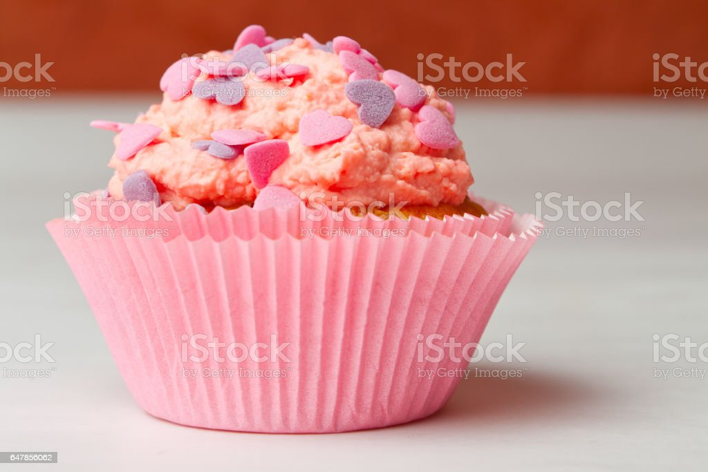 strawberry cupcake with icing sprinkles stock photo