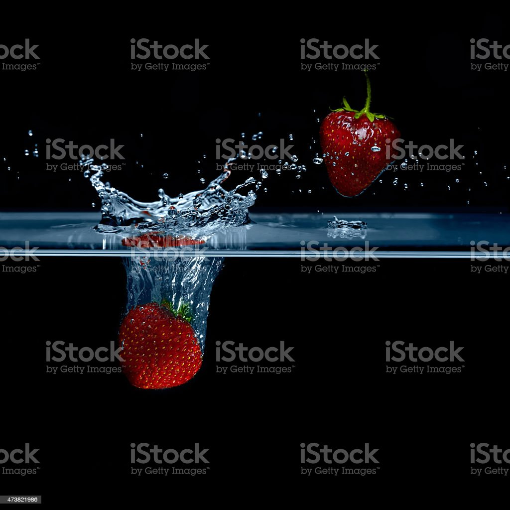 Strawberry falls into water. Strawberries in the air. Splash water. stock photo