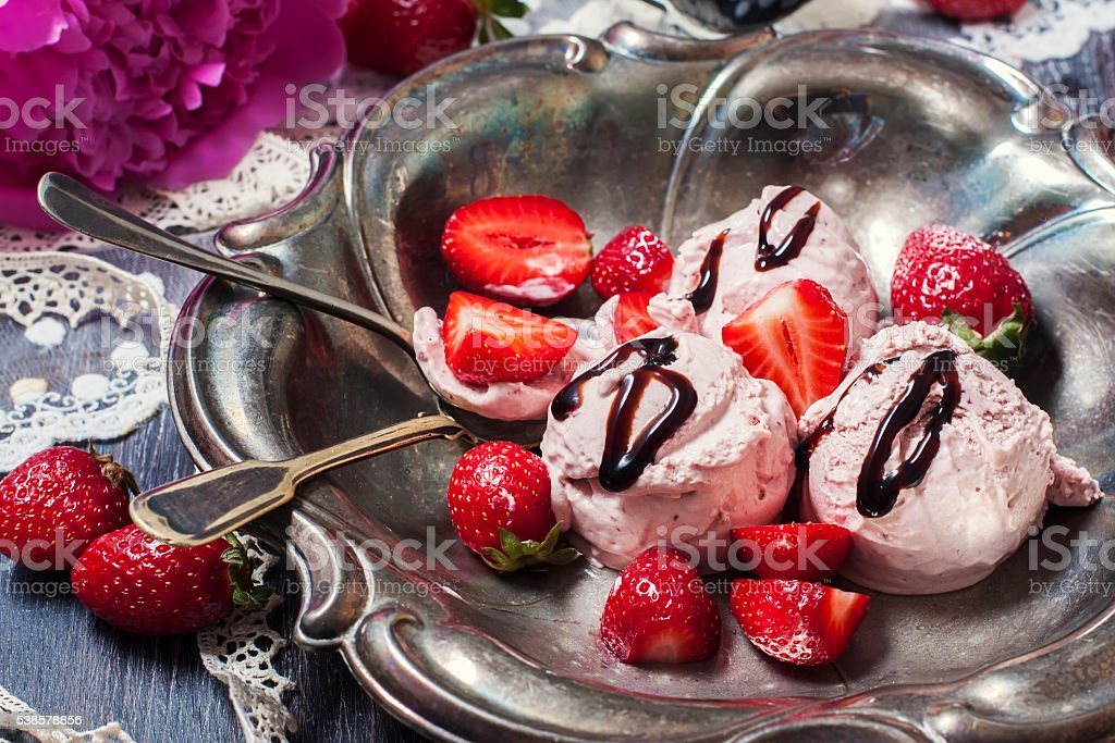 Strawberry ice cream with balsamic vinegar on a wooden backgroun stock photo