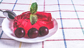 Strawberry jelly with cherries on the plate with ripe