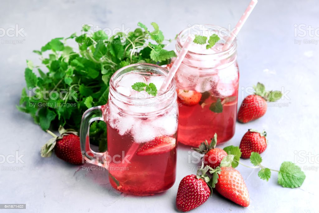 Strawberry lemonade with ice and mint in glass mug jars stock photo