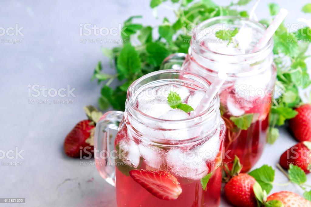 Strawberry lemonade with ice and mint in glass mug jars stock photo
