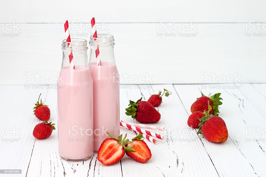 Strawberry milk in traditional glass bottles stock photo
