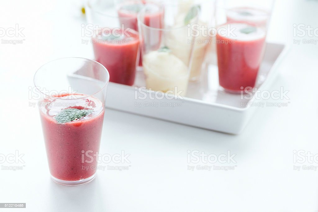 Strawberry mousse in a shot glass garnished with mint leaf. stock photo