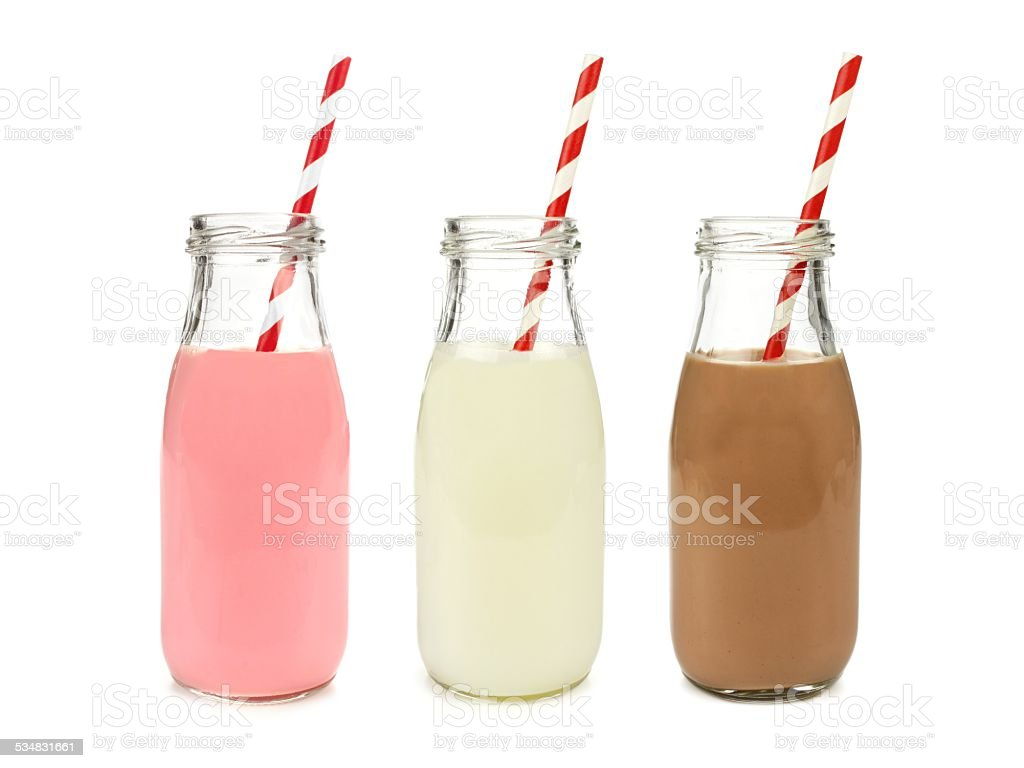 Strawberry regular and chocolate milk in bottles, isolated stock photo