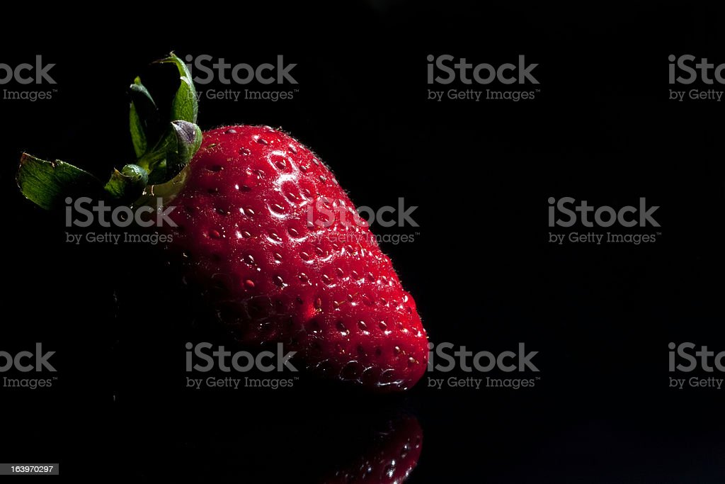 Strawberry single with drops isolated on black royalty-free stock photo
