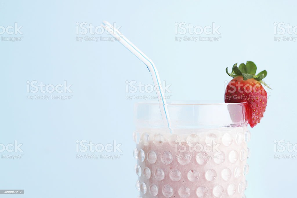Strawberry smoothie on blue background royalty-free stock photo