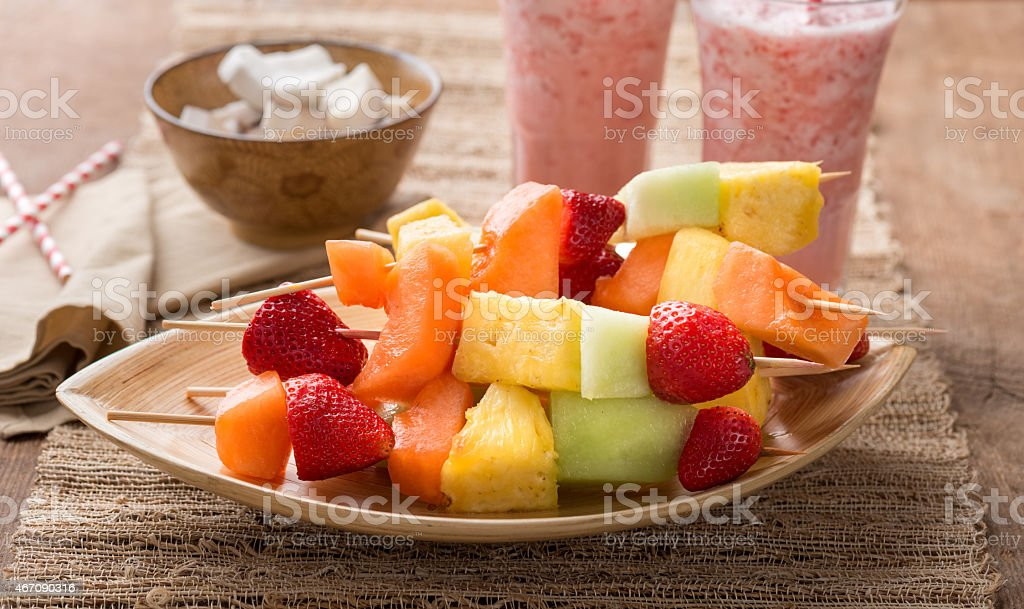 Strawberry smoothies and a bowl holding several fruit kabobs stock photo