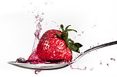Strawberry splashing water out of a spoon