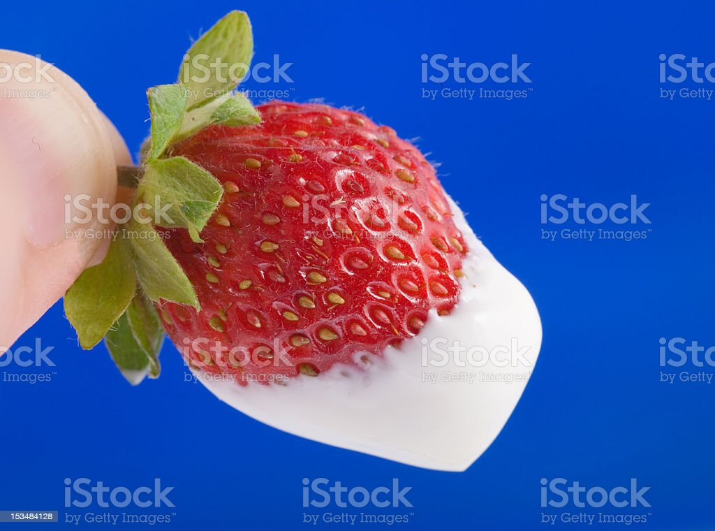 Strawberry with sour cream in the fingers royalty-free stock photo