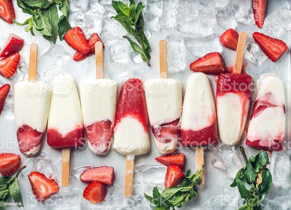 Strawberry yogurt ice cream popsicles with mint stock photo