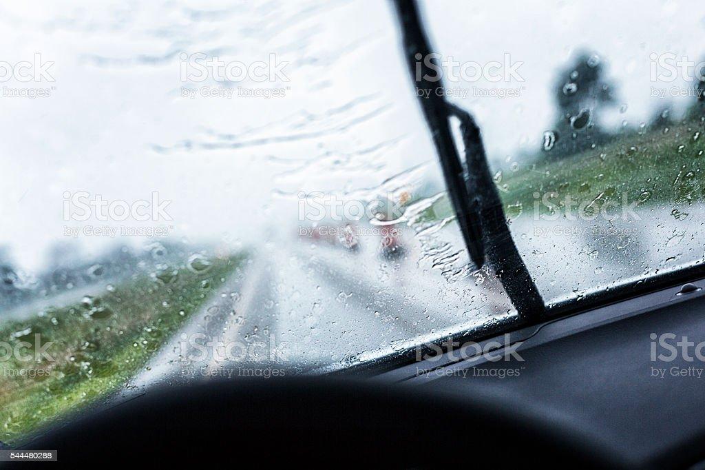 Streaking Rain Windshield Wiper Blade On Speeding Car Windshield stock photo