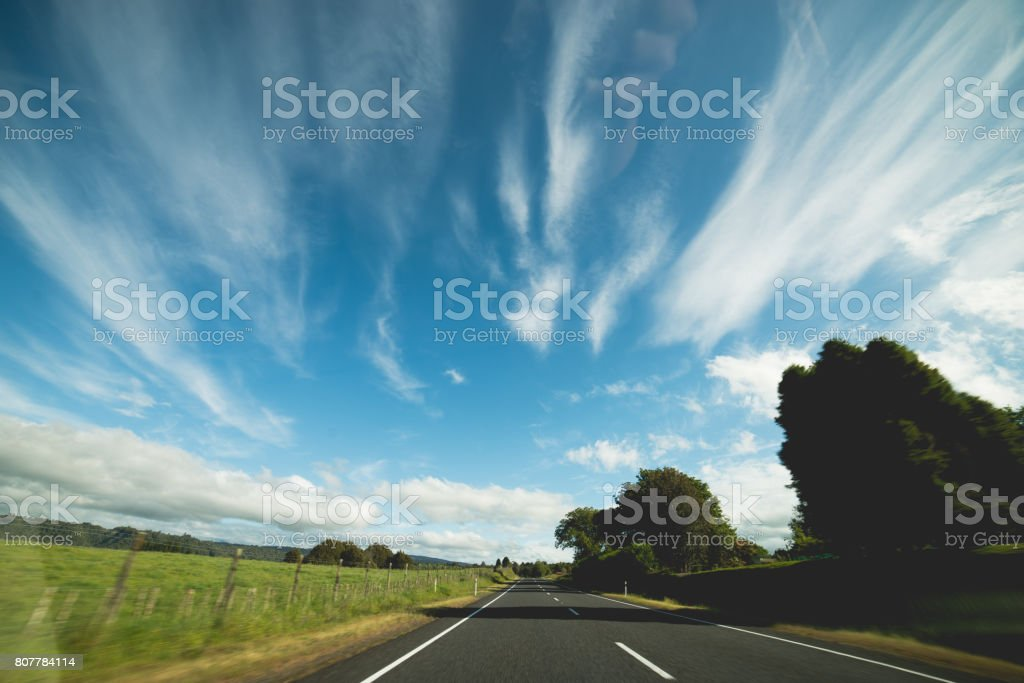 Streaks of clouds while driving along a road stock photo