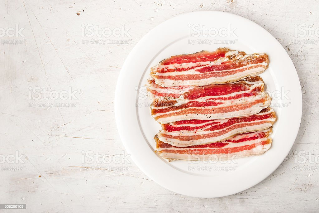 Streaky bacon on the white  scratched table top view stock photo