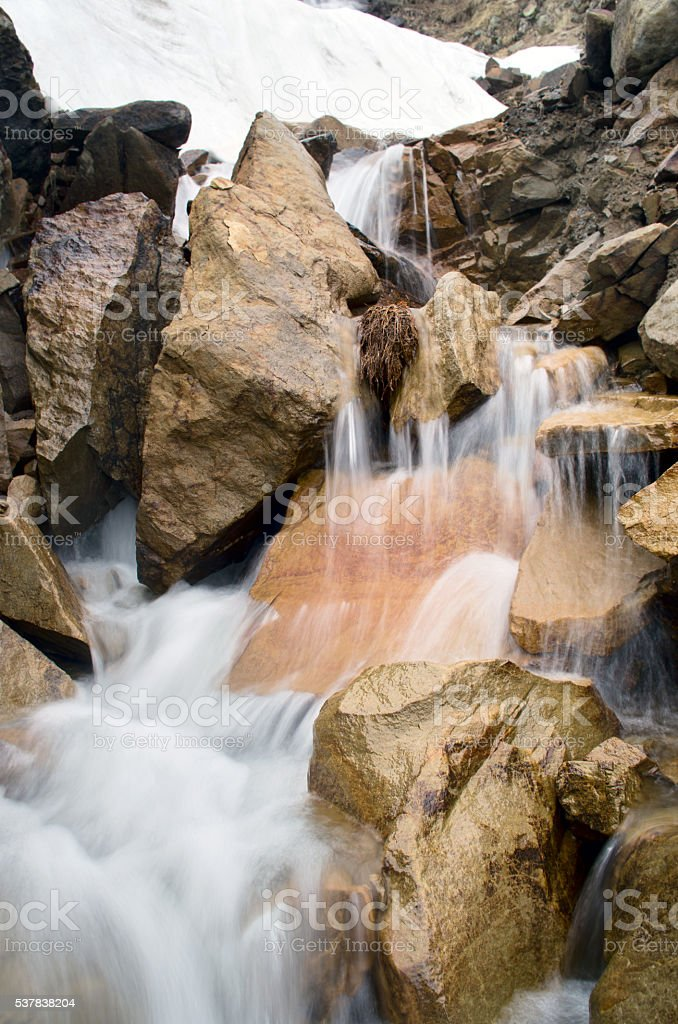 Stream among melting snow in a Carpathian Mountains stock photo