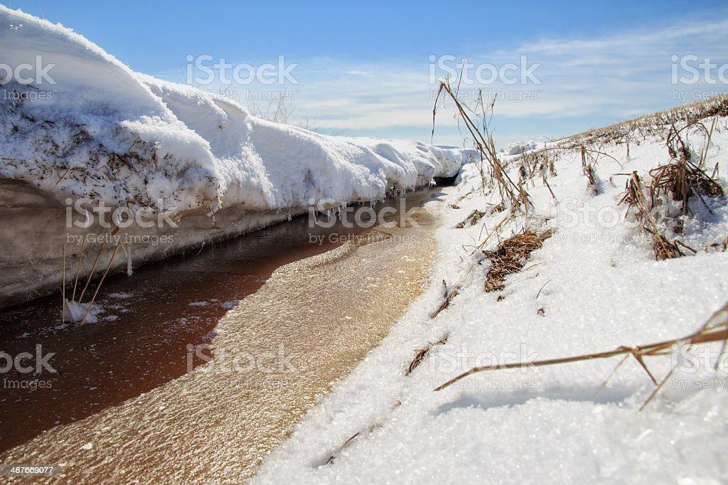 Stream carving through snow stock photo
