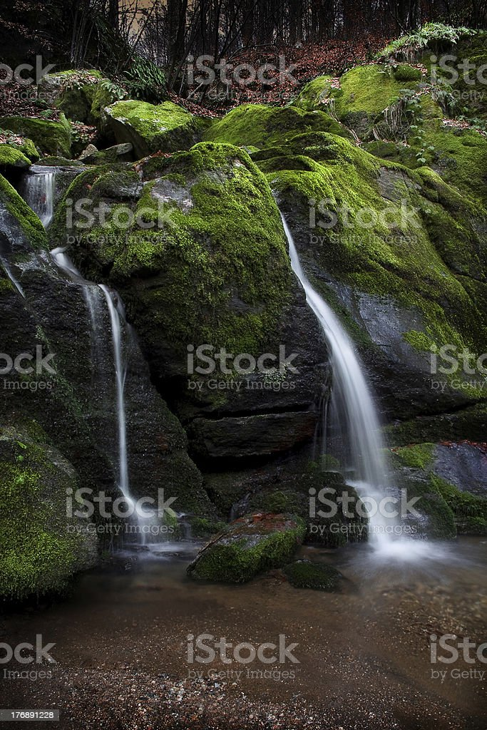 Stream flowing between the mossy rocks royalty-free stock photo