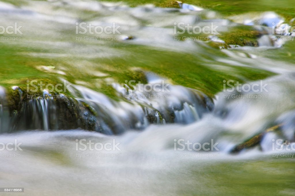 Stream Flowing over Mossy Rocks stock photo
