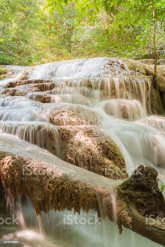 Stream flowing through foggy Autumn woodland at Erawan falls stock photo