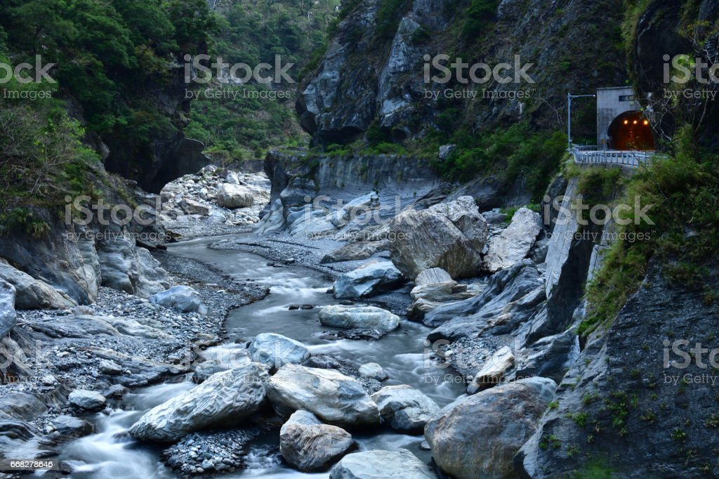 Stream flowing through mountain valley and cliff stock photo