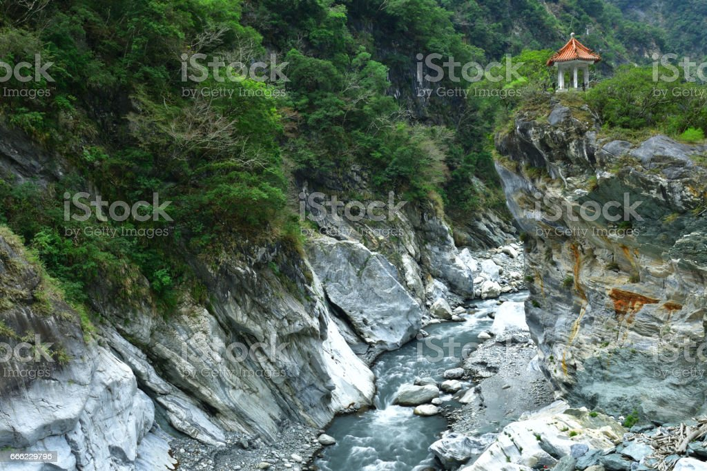Stream flowing through perpendicular cliff and mountain valley stock photo
