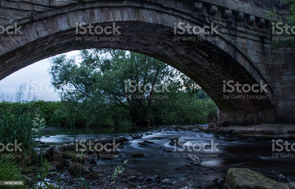 Stream flowing under a stone bridge stock photo