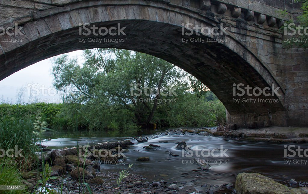 Stream flowing under bridge stock photo