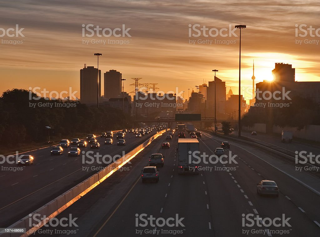 Stream of cars traveling on a busy highway at sunrise stock photo