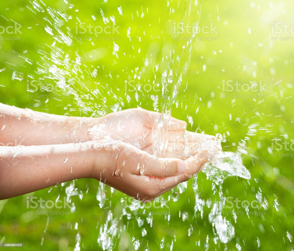 Stream of clean water pouring into children's hands stock photo