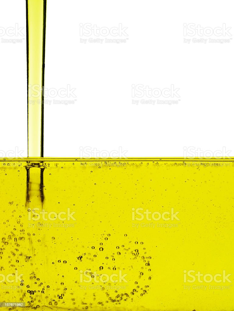 A stream of olive oil flowing into a pool of police oil stock photo