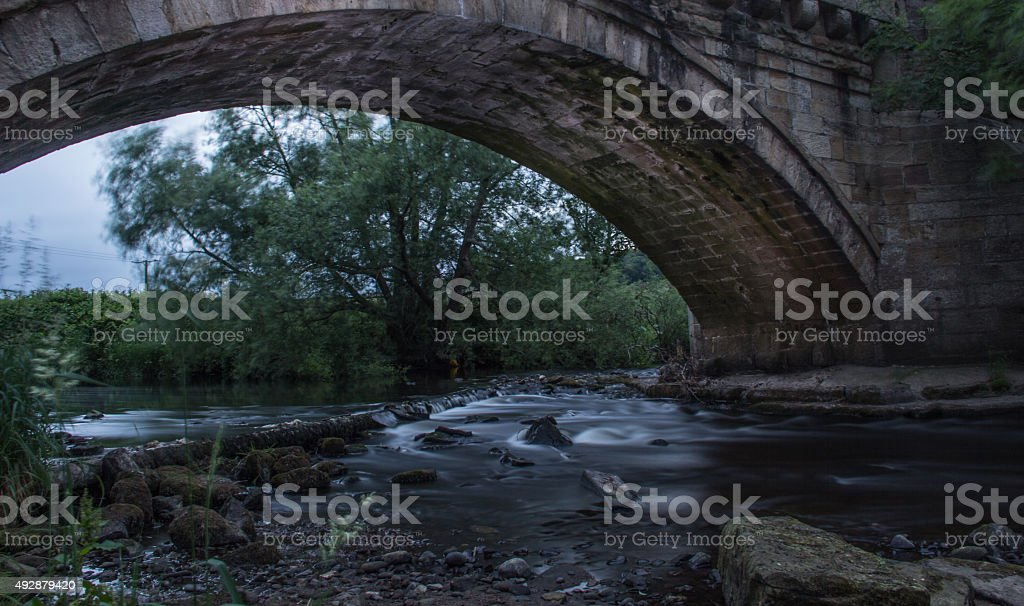 Stream under a stone bridge stock photo
