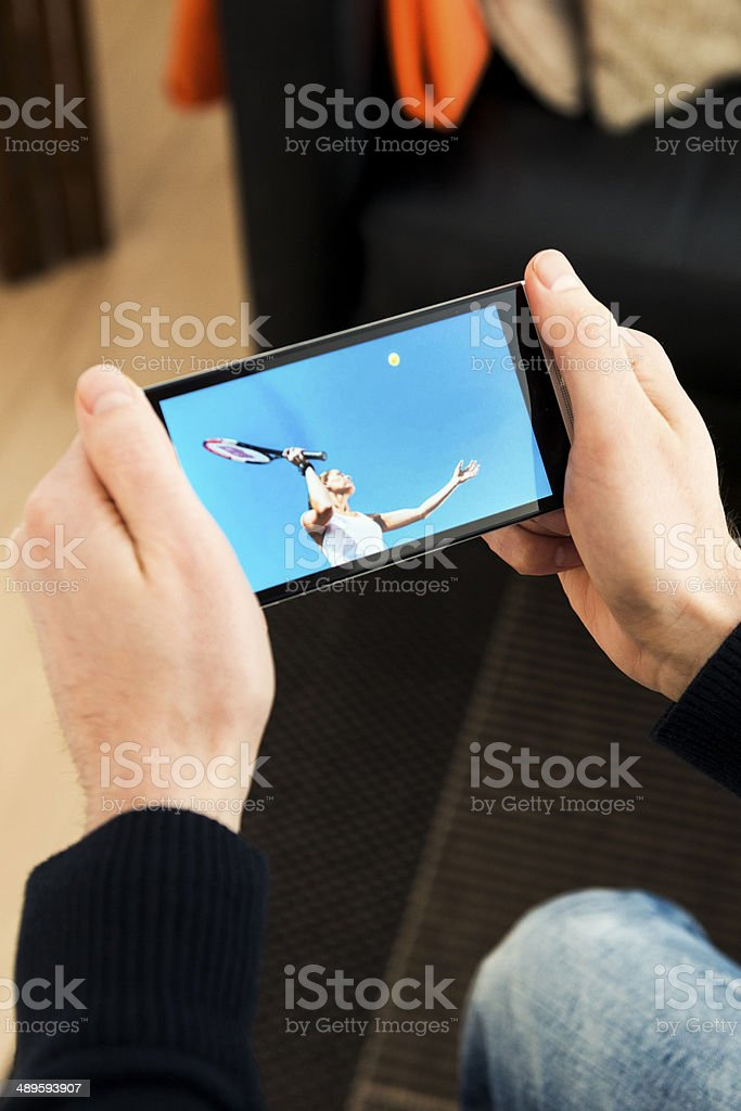 Streaming tennis match on a mobile phone stock photo