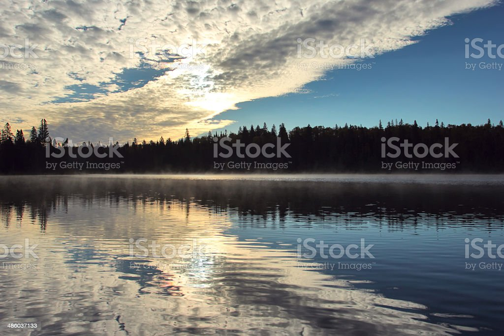 Streams of morning clouds on a beautiful lake royalty-free stock photo