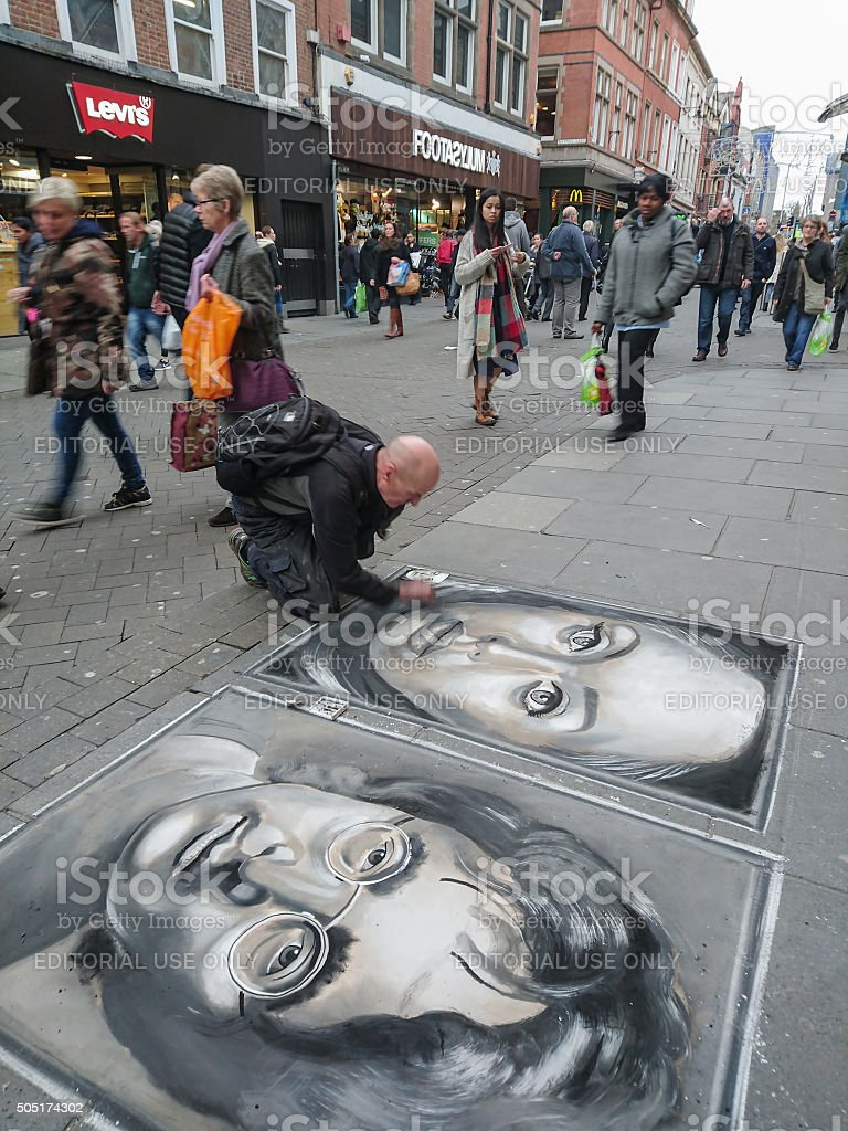 Street artist drawing chalk portraits on a pavement. stock photo